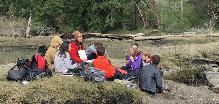 Alum Rebekah Gardea leads a group of School Overnight Program students during her time in the IslandWood Graduate Program.