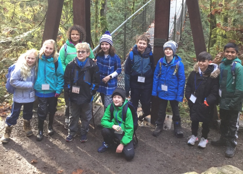 A group of School Overnight Program students pose in front of the Suspension Bridge.