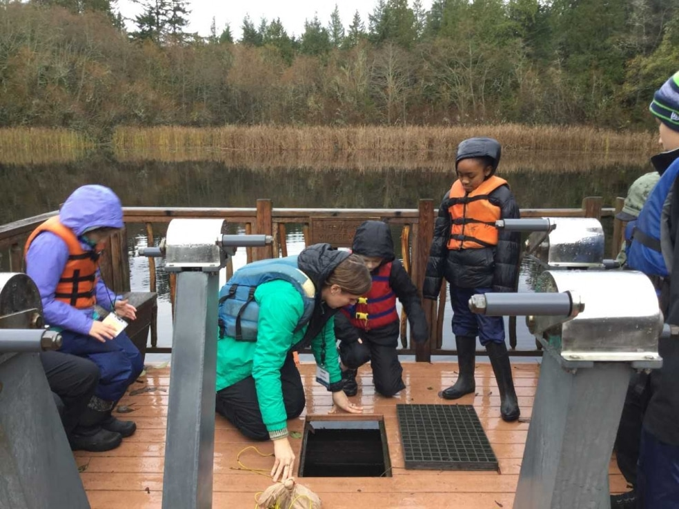 Graduate student Caroline Bargo and School Overnight Program students investigate Mac's Pond from the Floating Classroom.
