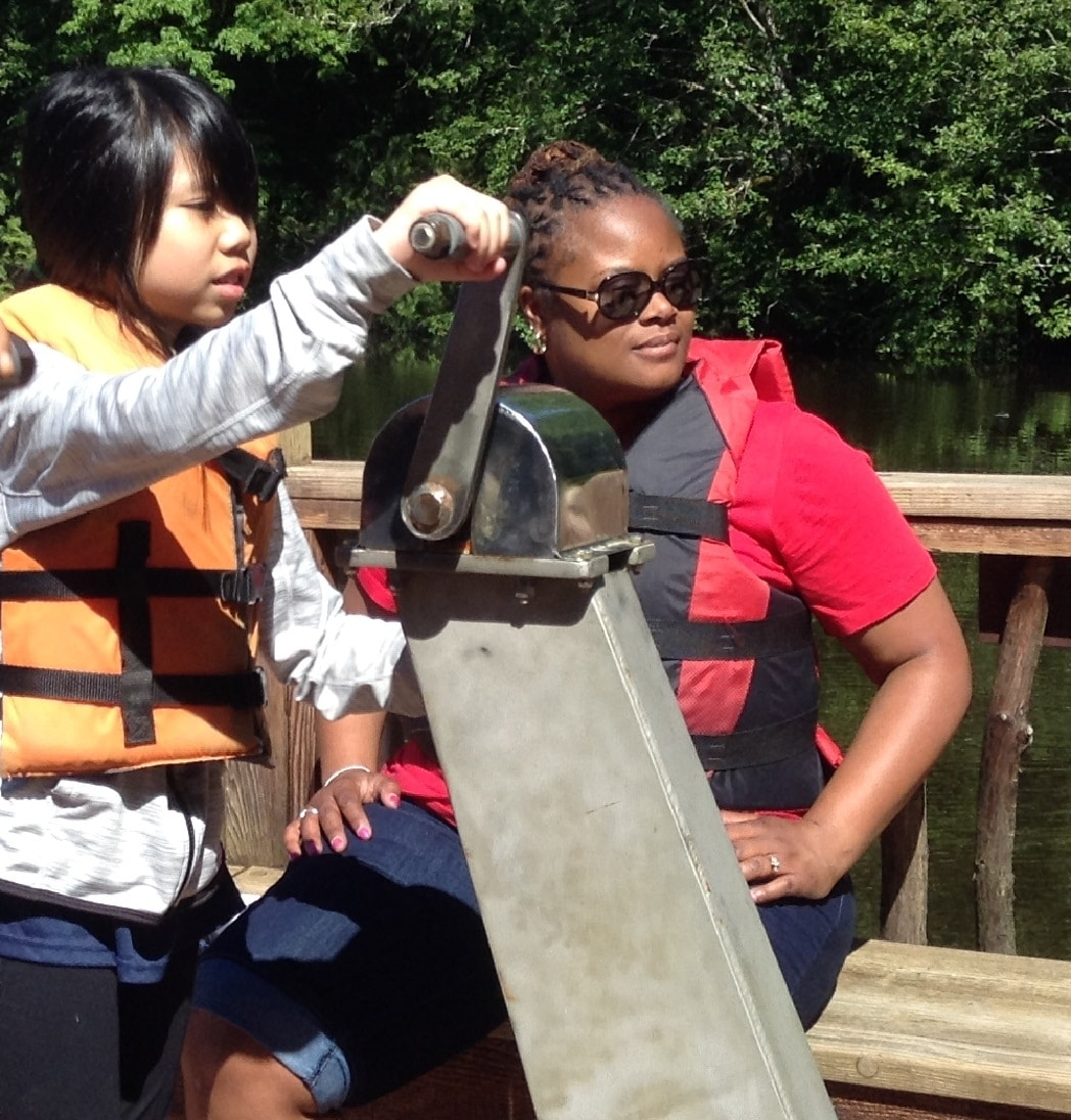Sartori Elementary School Principal Angela Sheffey Bogan sits on the Floating Classroom with students.
