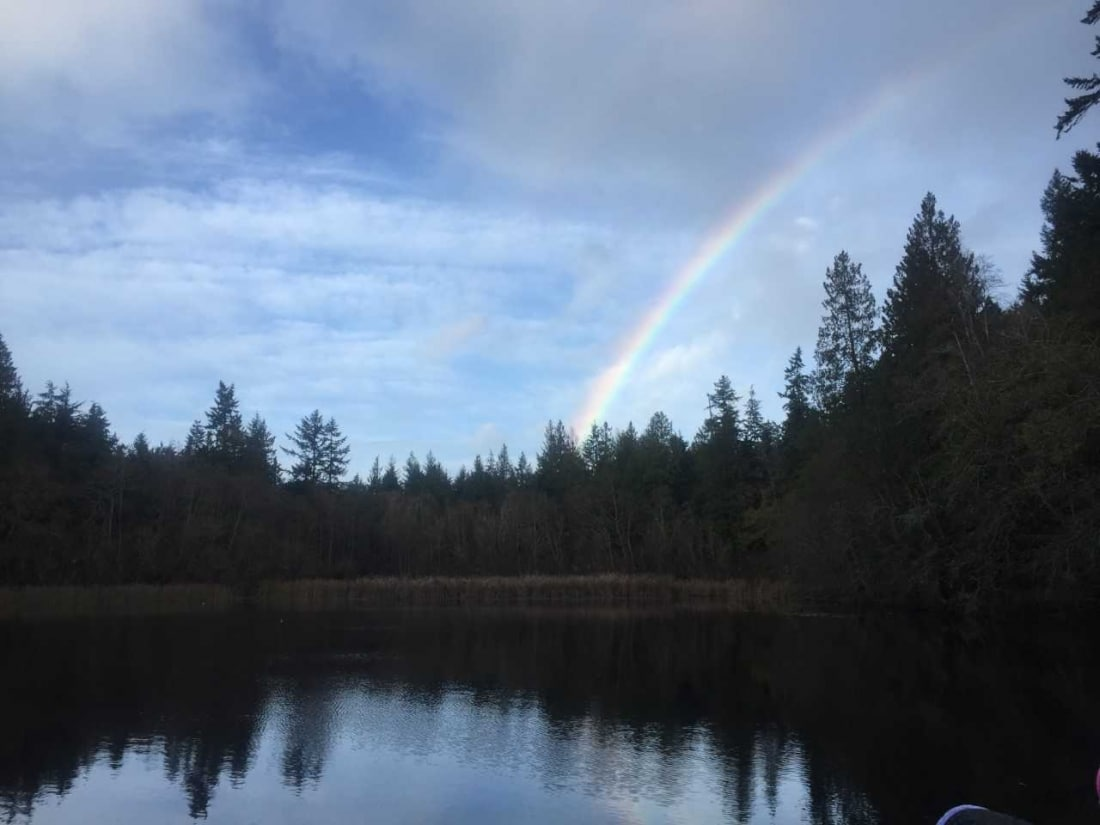 Mac's Pond with a rainbow in the sky behind it.