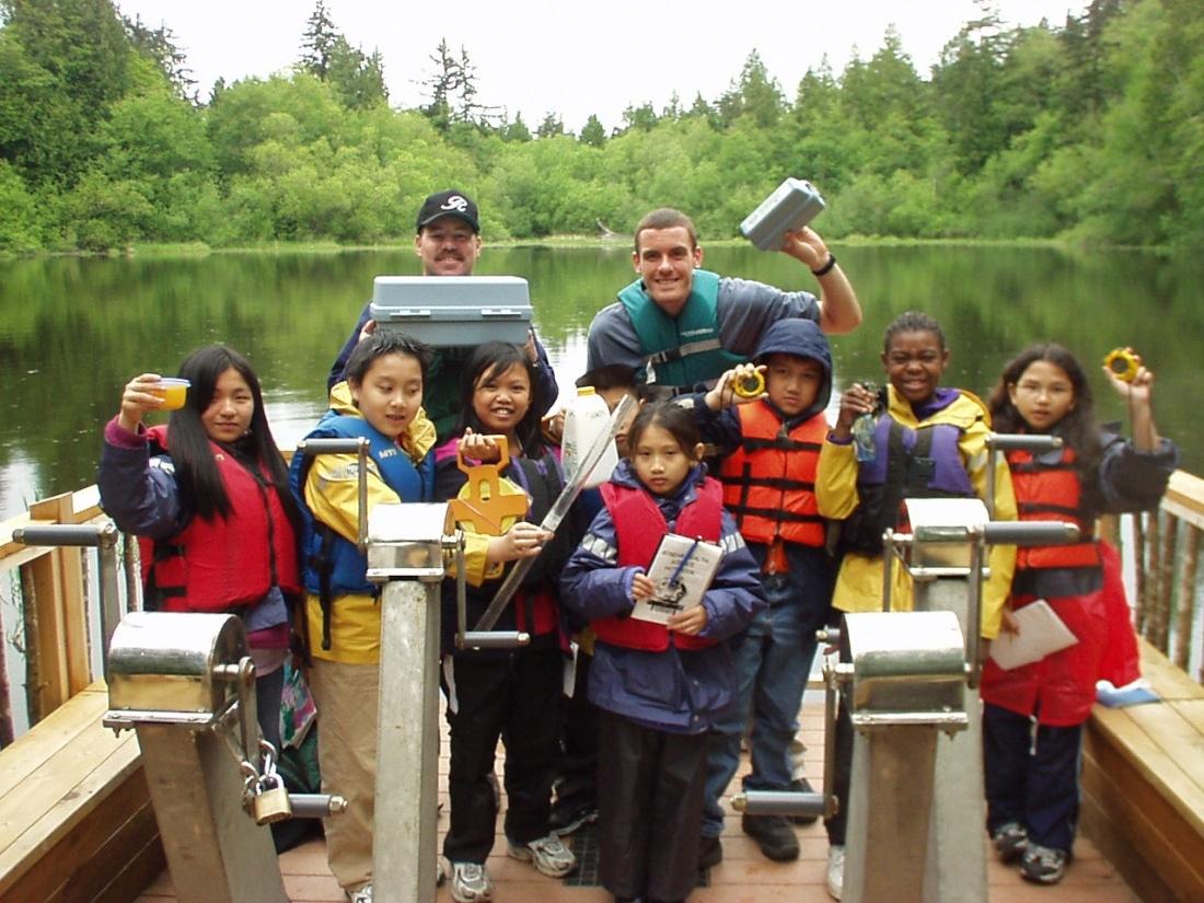 Joe Petrick leading a group of School Overnight Program students on the Floating Classroom on Mac's Pond.