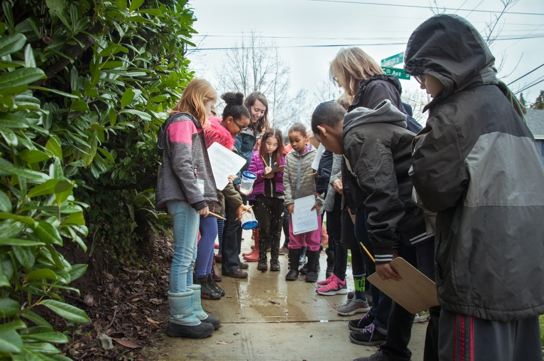Urban School Programs Coordinator Celina Steiger stands in a circle with Community Waters students while they investigate a puddle on the sidewalk.