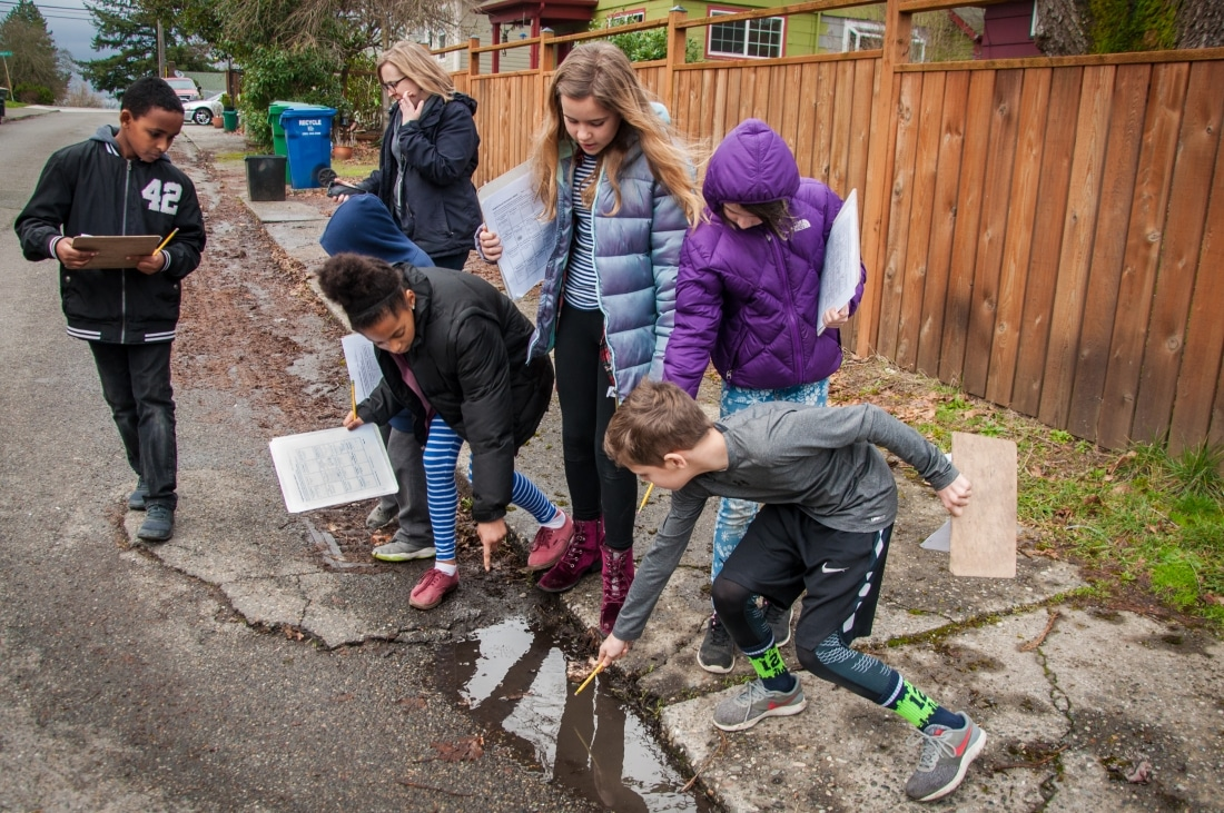 Students investigate a puddle in Seattle as part of the Community Waters Science Unit.