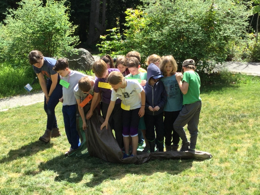 A group of School Overnight Program students participate in a team building exercise at islandWood.