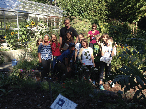 Steve Garlid poses with students and Garden Educator Jen Prodzinski in the garden.