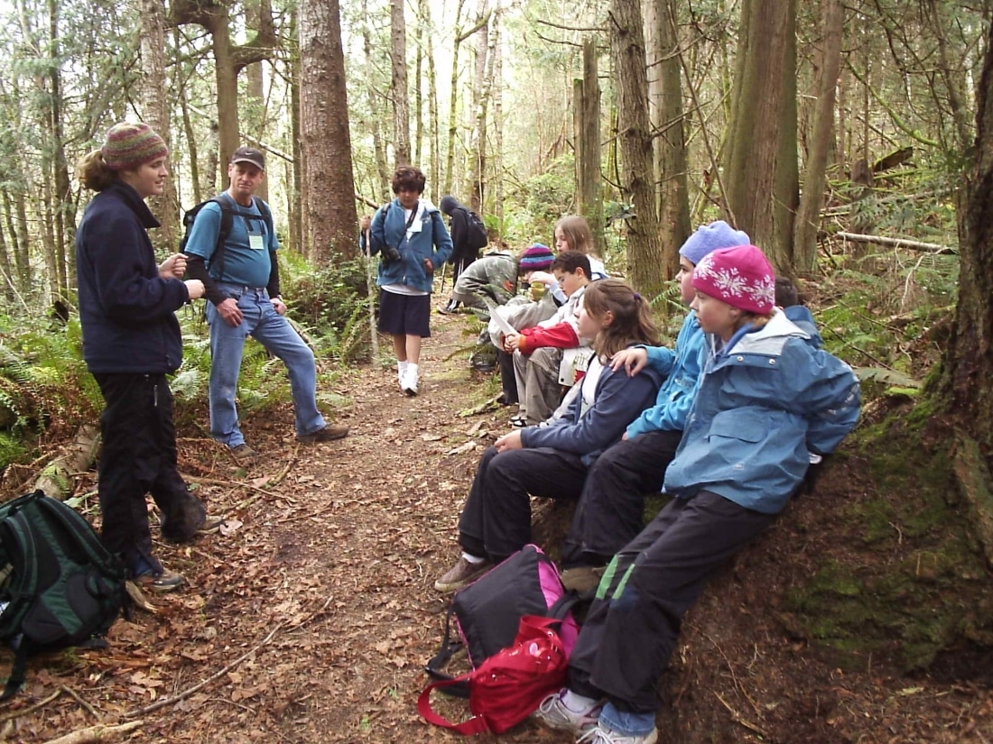 Lauren Watel as a graduate student at IslandWood, in the forest with School Overnight Program students.