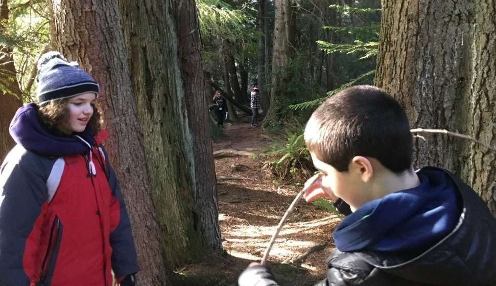 Two School Overnight Program students look at a twig together in the forest at IslandWood's Bainbridge Island campus.