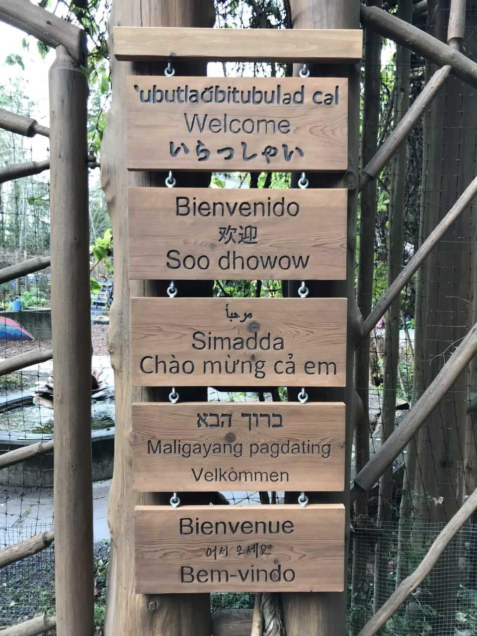 A close-up photo of the different languages represented on the garden welcome sign.