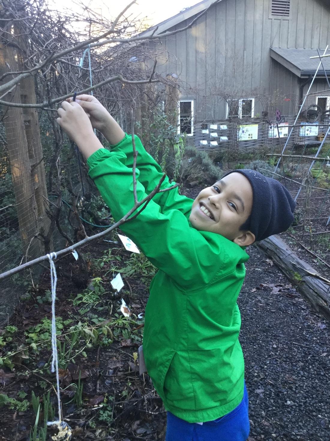 A School Overnight Program student hangs a bird feeder in the garden.