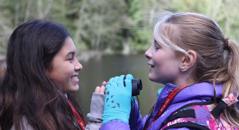 Two School Overnight Program students share binoculars on Mac's Pond.