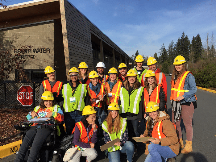 Déana Scipio posing in hard hats with graduate students at Brightwater.