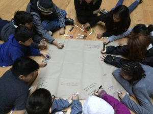 A circle of School Overnight Program students writing on a large piece of paper.