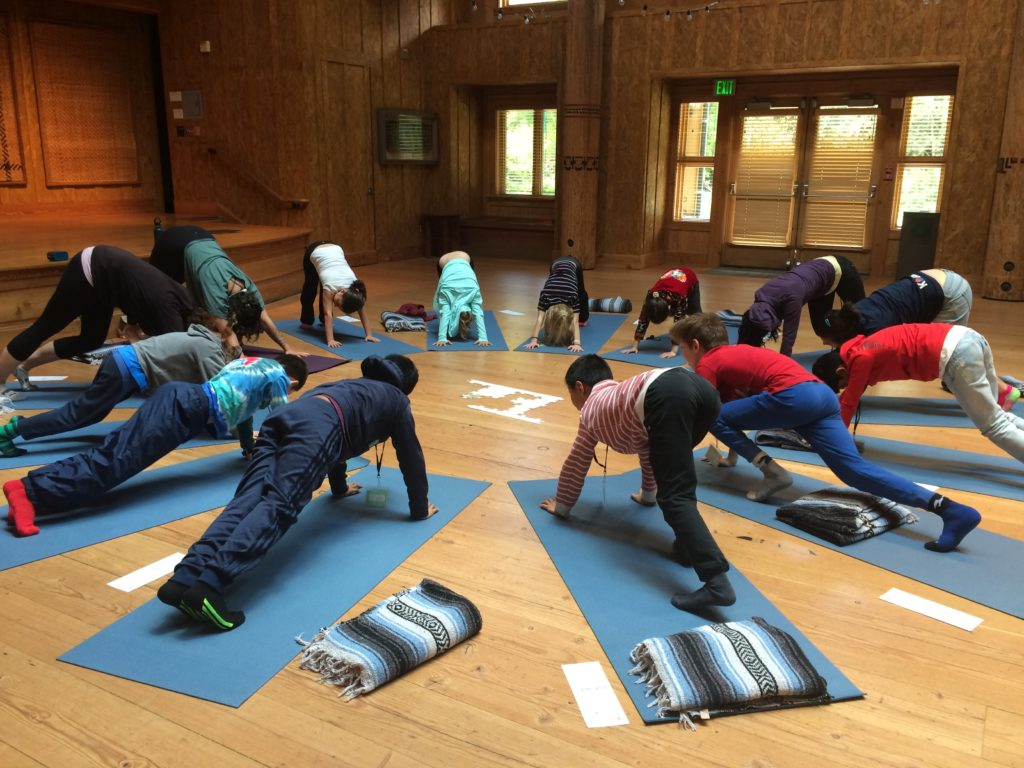 School Overnight Program students doing yoga in the Great Hall on IslandWood's Bainbridge Island campus.