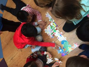 Students assemble a puzzle representing their communities.