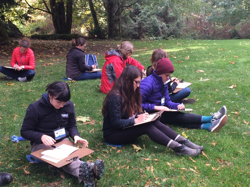 Graduate students nature journalling in a field.
