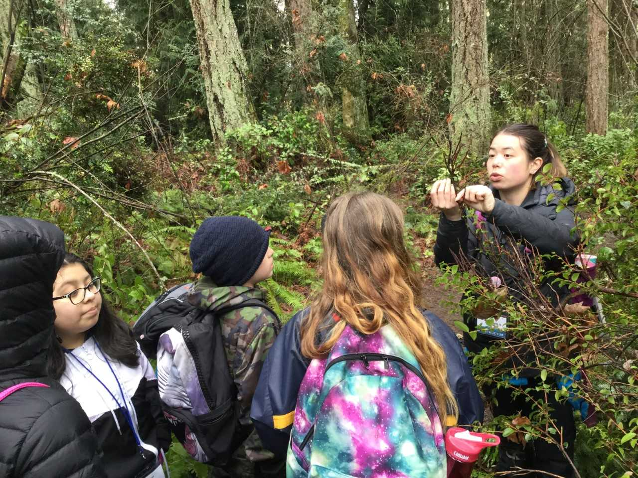 Graduate student Morgan Malley instructing School Overnight Program students in the forest.