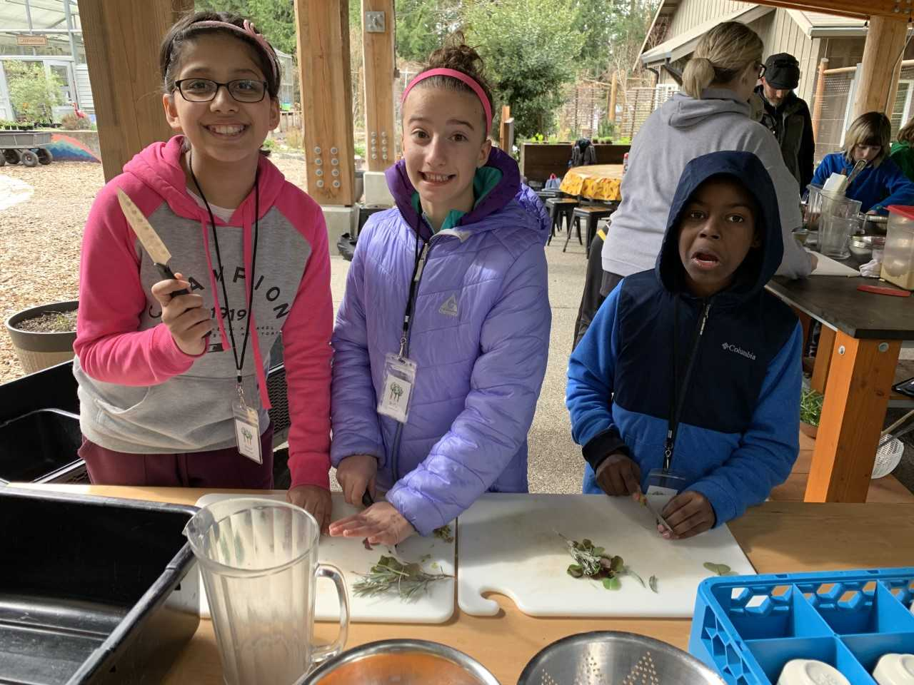 Three School Overnight Program students make food together in the garden.