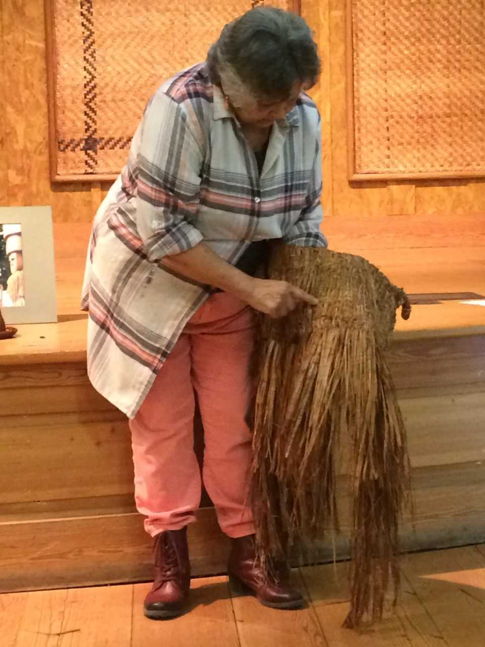 Peg Deam pointing at a detail in one of her cedar bark weavings.