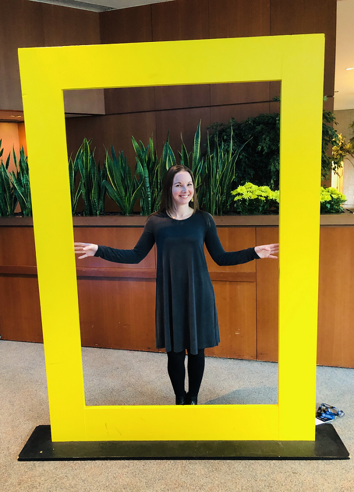 2018 Patsy Collins Award recipient Jennie Warmouth stands inside a National Geographic-style yellow frame. She is preparing to conduct research in the arctic beginning next week.