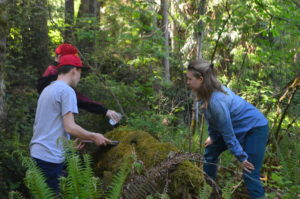 Nancyrose examining a log in the forest with campers.