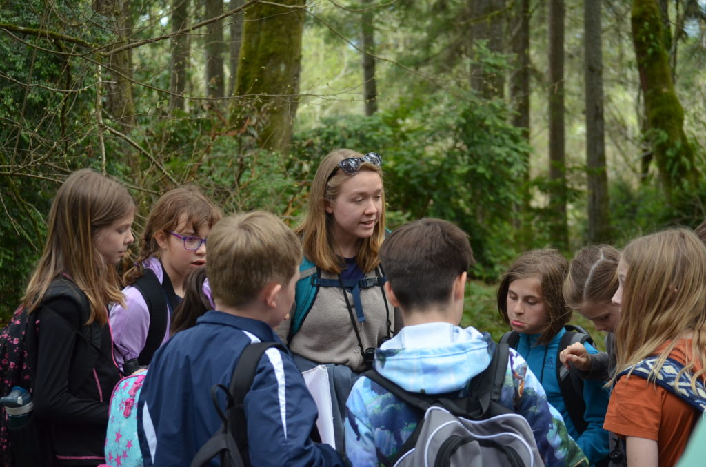 Nancyrose Houston gathers a group of students in a circle during an environmental education camp at Sound View.