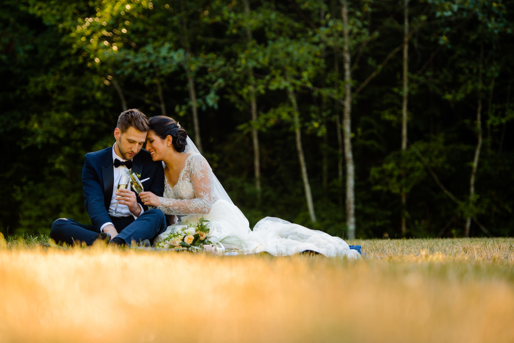 a wedding couple in a meadow at IslandWood, an Outdoor Wedding Venue