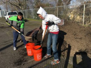 Volunteers load buckets of soil to fill beds at the garden Giorvi created in White Center.