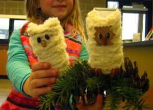 Child holding up her art projects. They are two owls made our of toilet paper rolls.