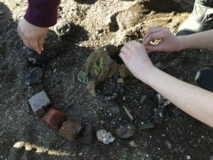 Students create a circle of stone in the sand at Blakely Harbor.