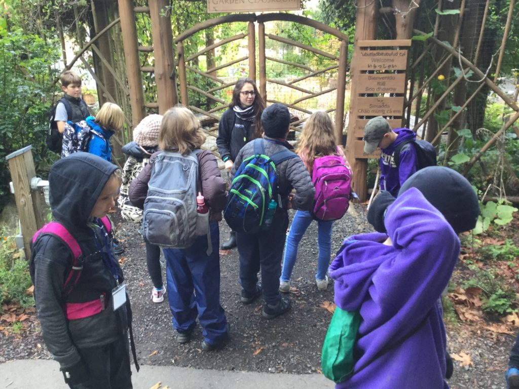 Kyleen stands outside of the IslandWood garden with a group pf School Overnight Program students.