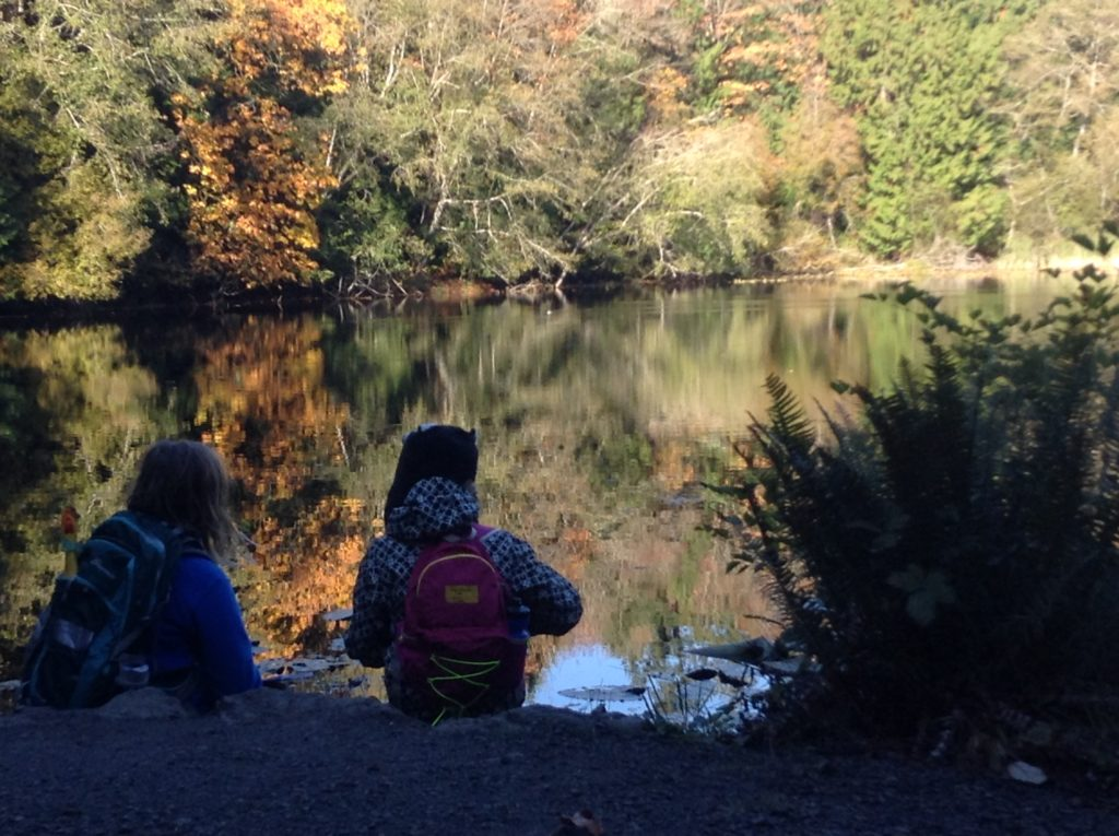 Two students sit on the bank of Mac's Pond.