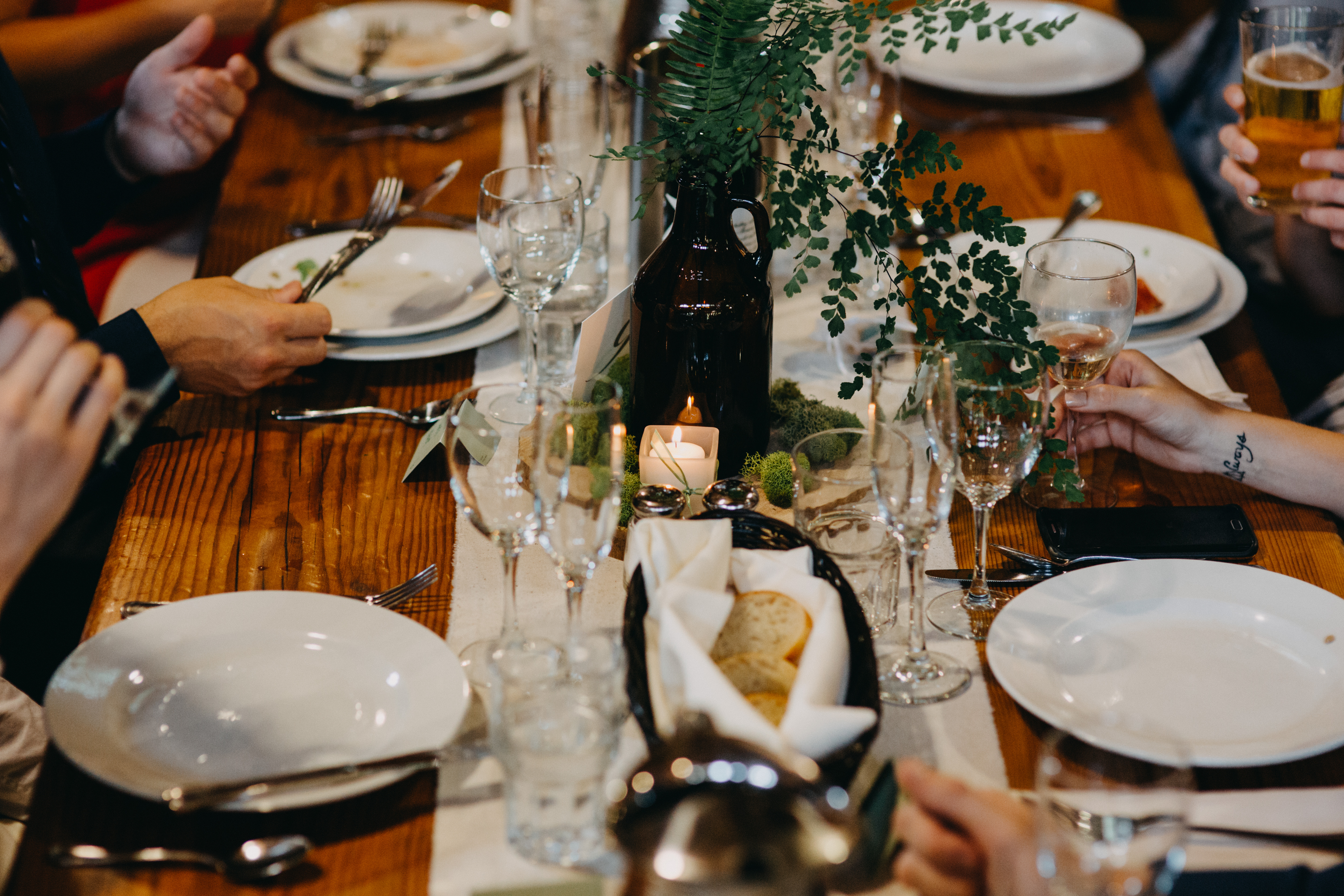 A table at IslandWood set with plates, a candle, a vase with a fern in it, and a basket of bread. Hands are visible on either side of the table, picking up silverware and wine glasses.