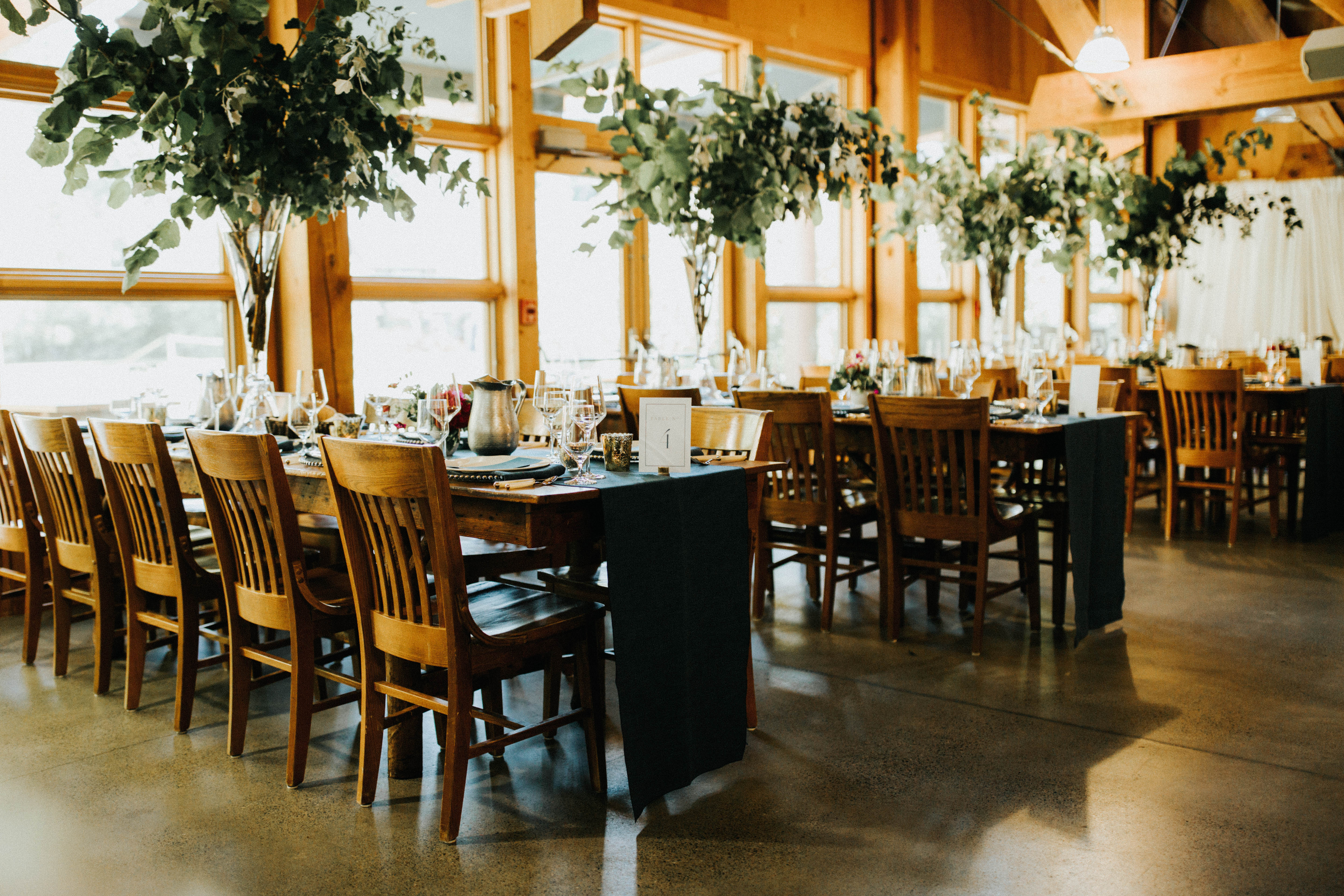 The Dining Hall at IslandWood. Three long tables are sewt with chairs and table settings. There are arrangements of greenery and florals above each table. Sunlight is streaming in from the windows behind the tables at IslandWood, an Outdoor Wedding Venue