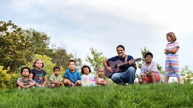 [Image description: Joe Reilly sits with a group of kids in a grassy field. He is holding his guitar.]