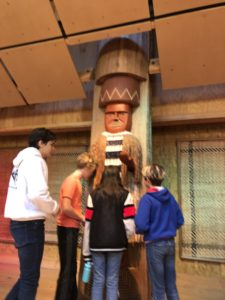 [Image description: four students look at the house post in IslandWood's Great Hall.]