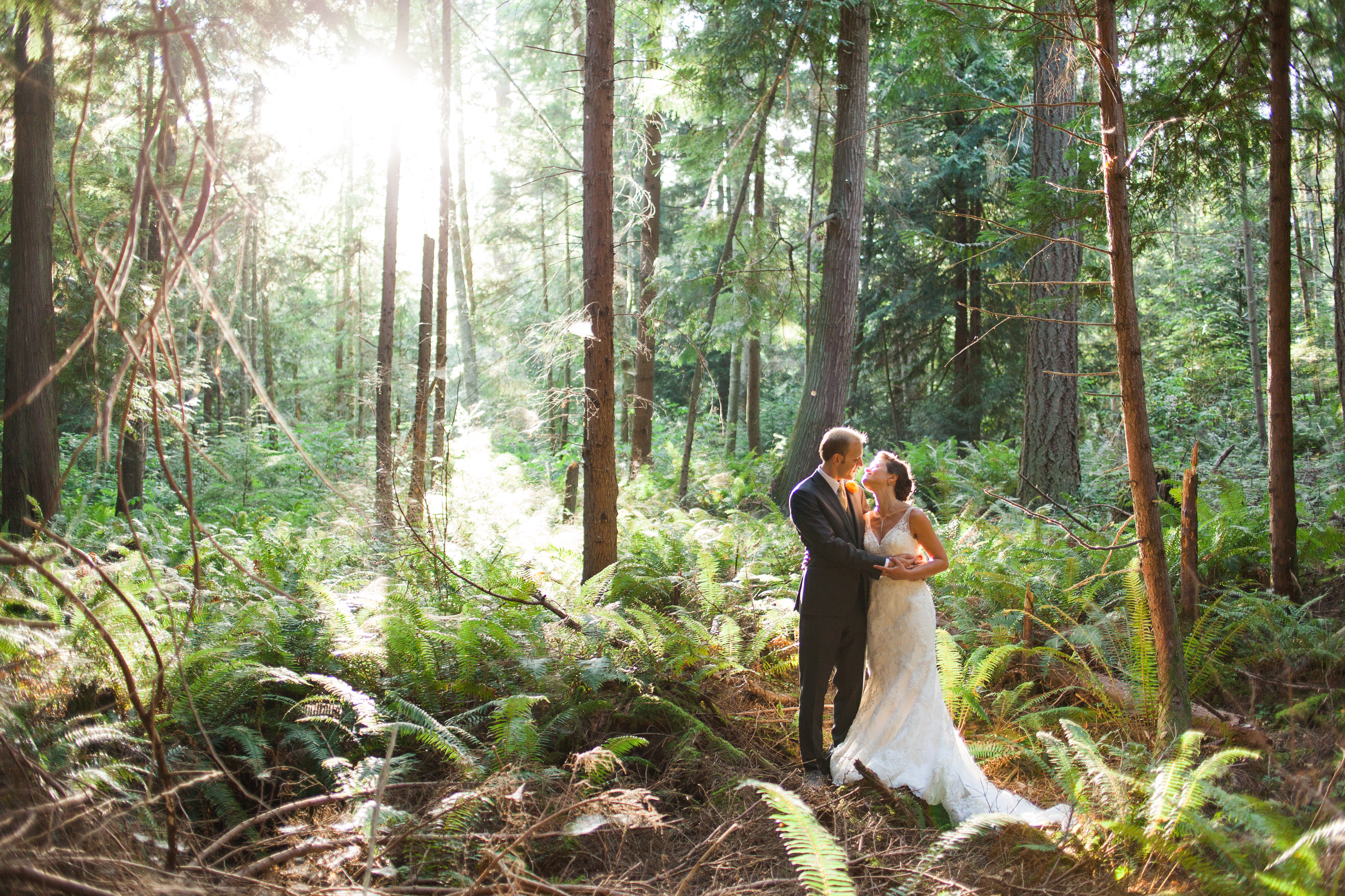 [Image description: a couple smile with their arms around each other in the forest at IslandWood.]