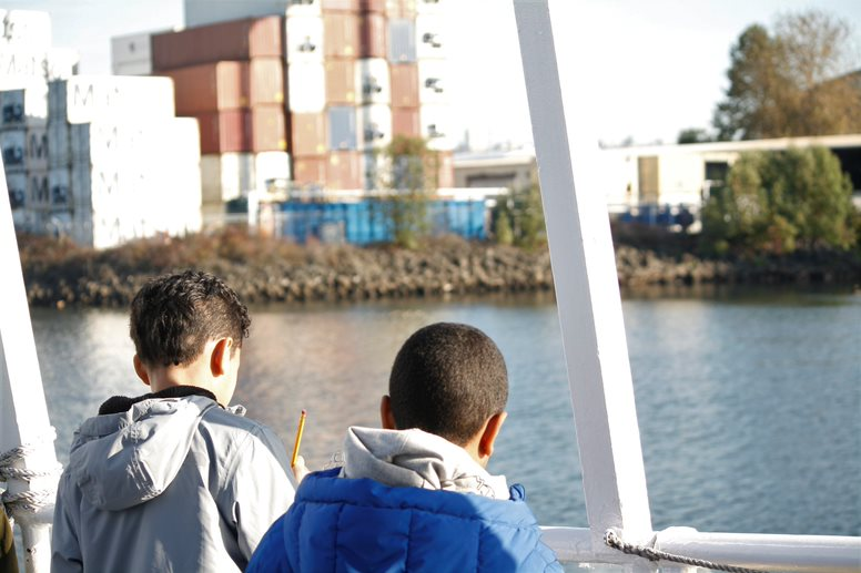 A photo of two students on the Argosy boat during the Duwamish River Program. The backs of their heads are visible and they are looking in the direction of a pile of shipping containers on the bank of the Duwamish River.
