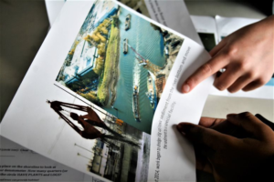 [Image description: A student holds a handout showing photos of a cleanup effort on the Duwamish River. Another student is pointing at the text on the handout.]