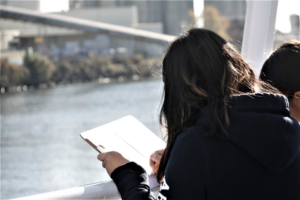 [Image description: A student writes notes on a piece of paper on the deck of the Argosy boat. The river and the river bank are visible in the background.]