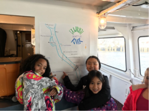 A photo of three students on the Argosy boat during the Duwamish River Program. They are posing in front of a drawn map of the river.