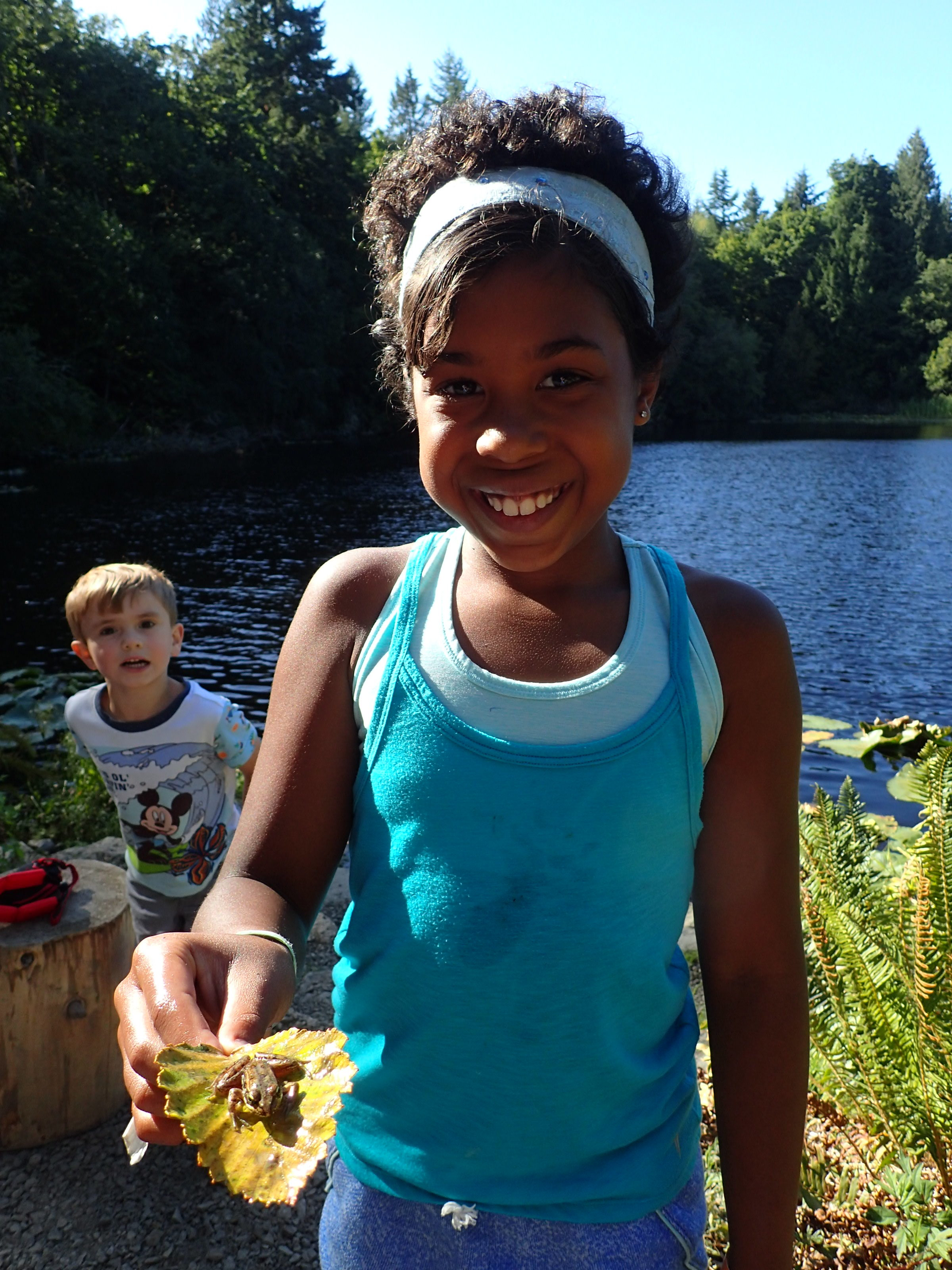 [Image description: a photo of a child holding a frog in their hand at Mac's Pond on IslandWood's Bainbridge Island campus.]
