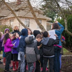 [Image description: Urban School Programs Coordinator Celina Steiger leads a group of students in a walking field trip through a Seattle neighborhood.]
