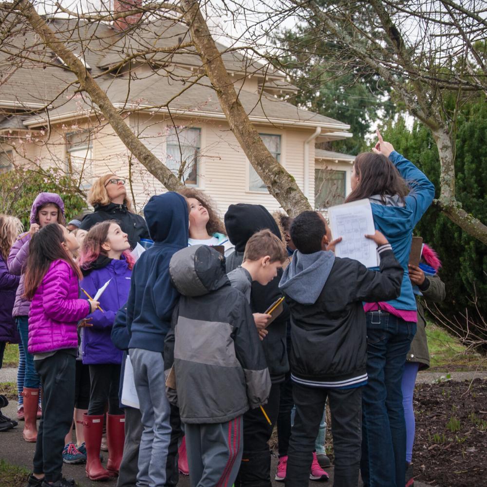 [Image description: Urban School Programs Coordinator Celina Steiger leads a group of students in a walking field trip through a Seattle neighborhood.]