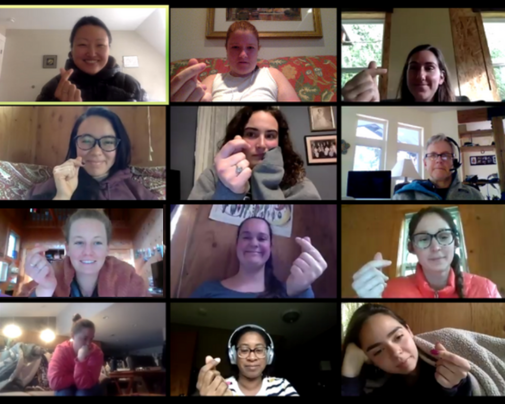 "[Image description: IslandWood graduate students, staff, and faculty members hold up ""finger hearts"" during a Zoom video call.]"