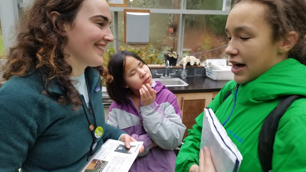[Image description: IslandWood graduate student and School Overnight Program instructor Taylor O'Connor smiles as she talks to two students from the Washington State School for the Blind.]