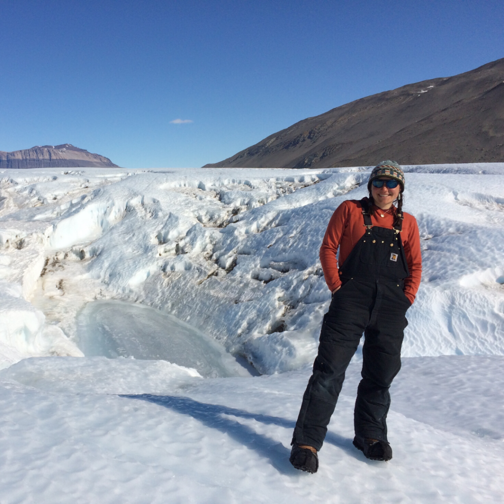 [Image description: Heidi Roop stands with her hands in her pockets on a glacier. She is smiling. Behind her, the sky is blue and hills are visible in the background.]