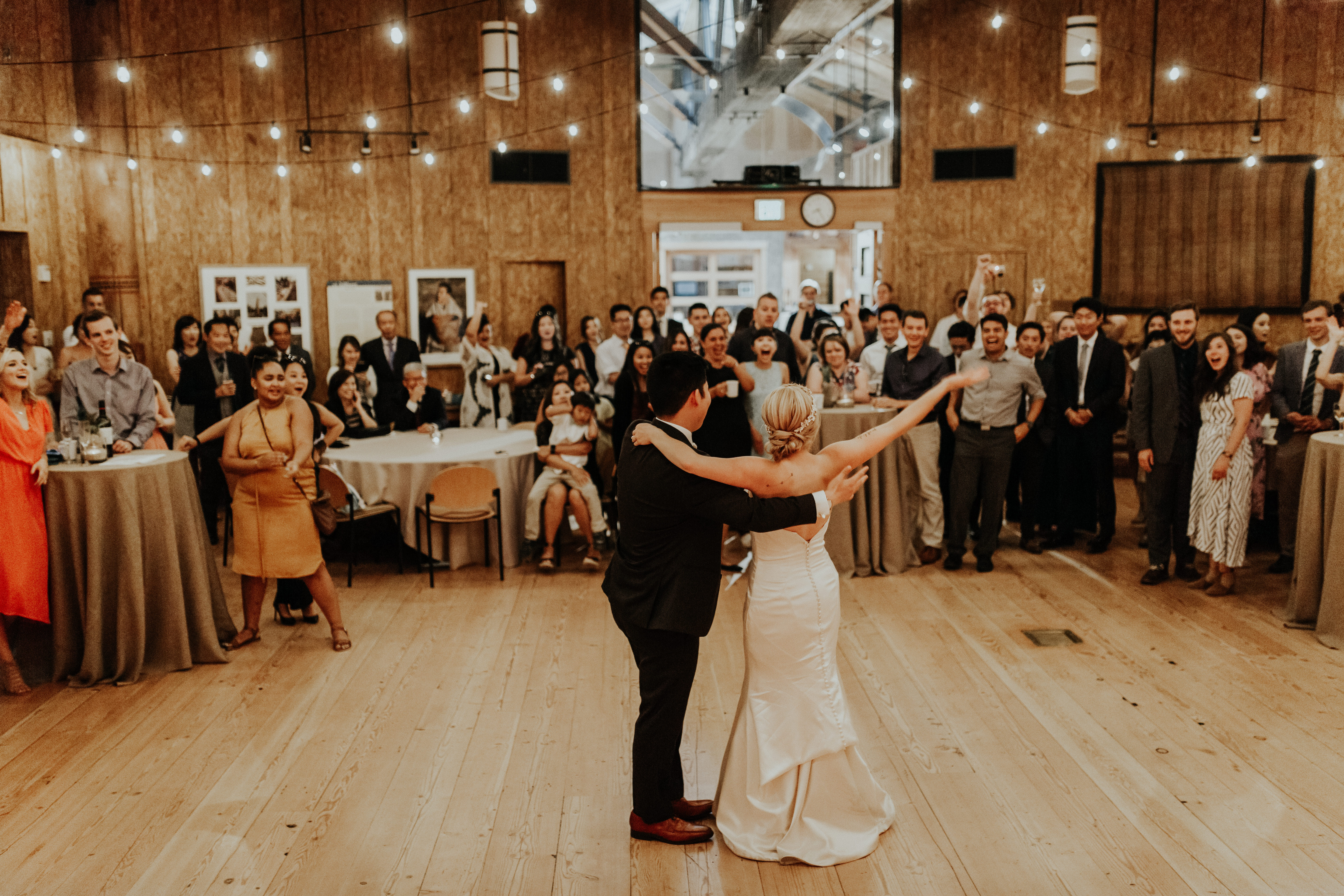 [Image description: a wedding couple faces away from the camera with their arms outstretched in the Great Hall. Their wedding guests are in front of them, clapping and smiling.]