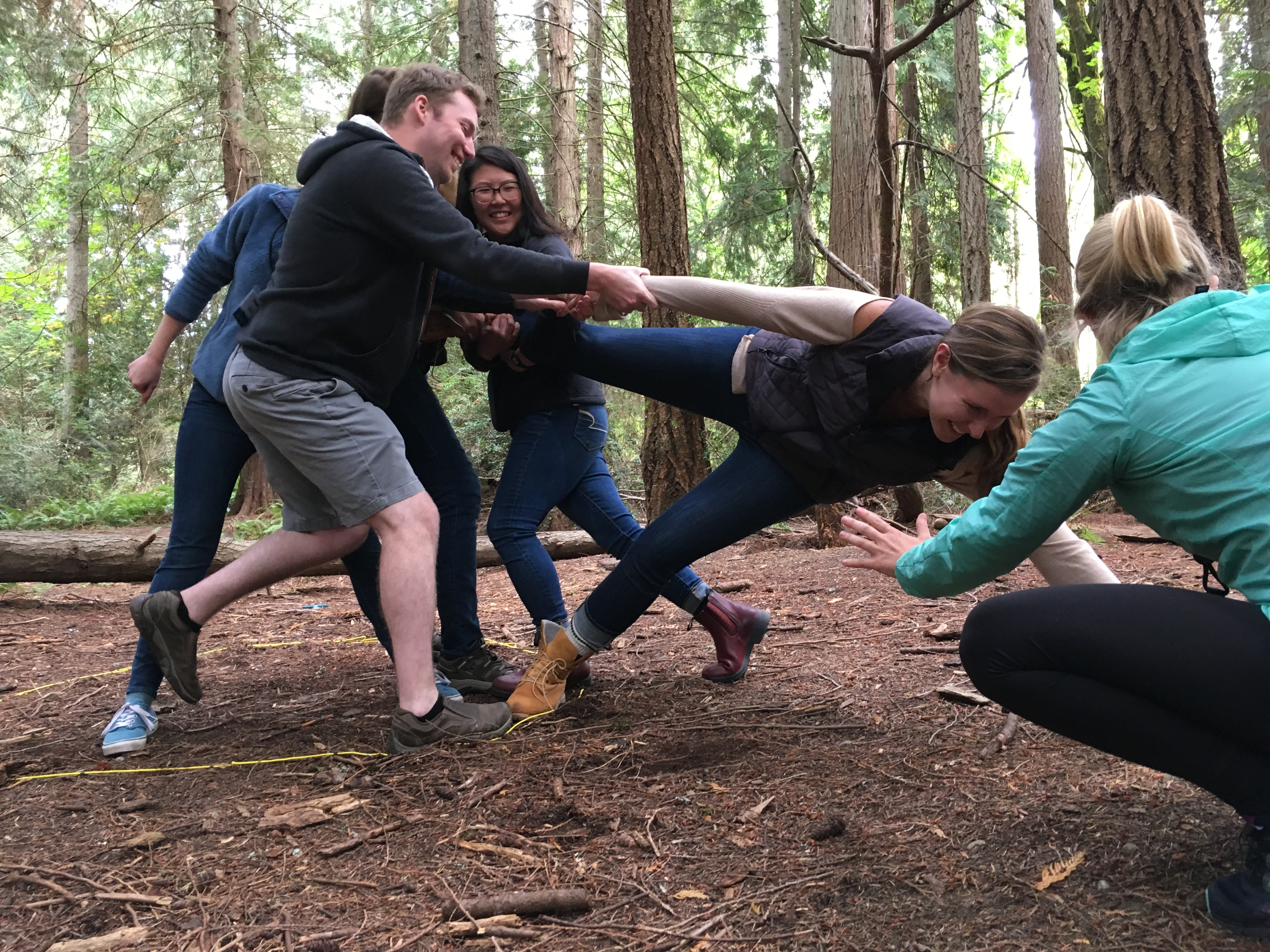 [Image description: graduate students participate in a team-building game in IslandWood's forest.]