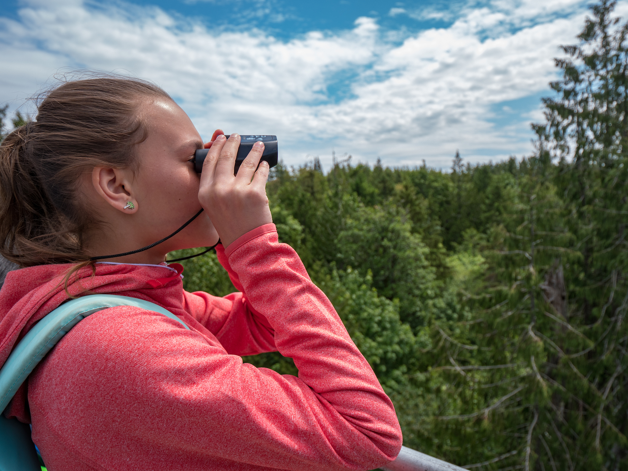 A student looks through binoculars at the top of the Canopy Tower on IslandWood's Bainbridge Island campus.